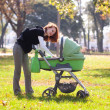 Young mother carrying baby in autumn park — Stock Photo #7226806