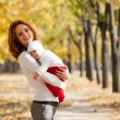 Young mother with sleeping child on hands in autumn park — Stock Photo
