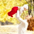 Stock Photo: Young mother playing with daughter in autumn park