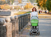 Happy young mother with baby in buggy — Stock Photo