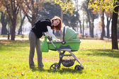 Young mother carrying baby in autumn park — Stock Photo