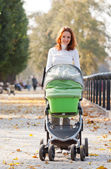 Happy young mother with baby in buggy — ストック写真