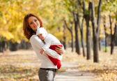 Junge mutter mit kind auf schlafen hände im herbst-park — Stockfoto