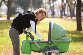 Young mother carrying baby in autumn park — ストック写真