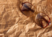 Antique glasses on old crumpled paper — Stock Photo