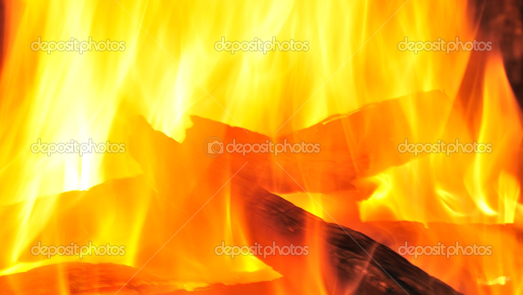 Yellow flames of a fire through which burn logs — Stock Photo #6861912