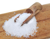 Salt on wooden board with spoon — Stock Photo