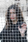 Girl behind the net — Stock Photo