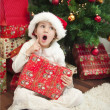 Child with gift in front of christmas tree - Stok fotoğraf