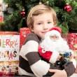 Child with santa doll in front of christmas tree — Photo