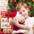 Child with santa doll in front of christmas tree — Stok fotoğraf