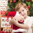 Child with santa doll in front of christmas tree — Стоковая фотография
