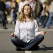 Woman meditating in busy urban street — Stock Photo #7658921