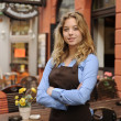 Photo: Waitress in front of restaurant