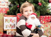 Child with santa doll in front of christmas tree — Foto Stock