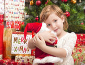 Child with santa doll in front of christmas tree — Stock Photo