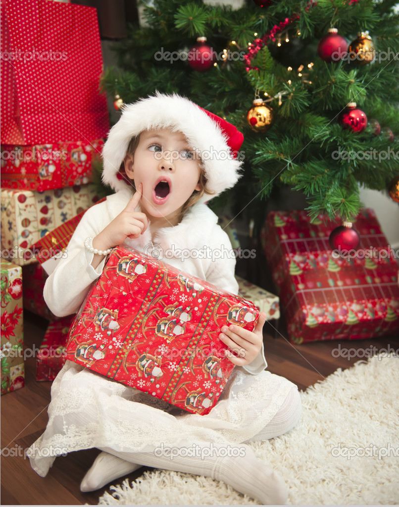 Cute child with gift in front of christmas tree  Stock Photo #7658898