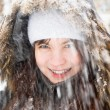 Laughing girl under snow — Stock Photo
