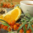 Tea with fruits of sea buckthorn and oranges — Stock Photo