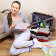 Young woman packing suitcase — ストック写真