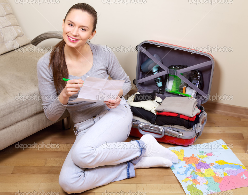 Young woman packing a suitcase at home going on holiday — Stock fotografie #6746060