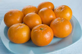 Ripe fresh tangerine on blue plate — Stock Photo