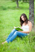 Outdoor portrait of a cute reading teen — Stock Photo