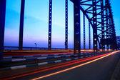 Light trails through the steel bridge — Stock Photo