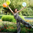 Joyful pregnant girl with colorful balloons walking in park — Stock Photo