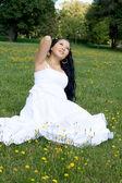 Bella ragazza incinta, seduto sull'erba — Foto Stock