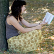 Girl reading book in park — Stock fotografie
