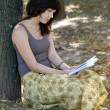 Stock Photo: Girl reading book in park