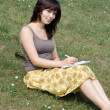 Girl sitting on grass in park — Stock Photo #6902288