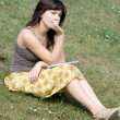 Girl sitting on grass in park — Stock Photo #6902308