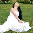 Beautiful pregnant girl sitting on grass — Stok fotoğraf