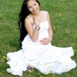 Beautiful pregnant girl sitting on grass — Stockfoto