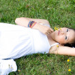 Beautiful pregnant girl lying on grass — Stock fotografie
