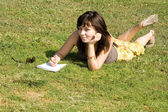 Girl lying on grass in park — Photo