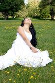 Hermosa chica embarazada sentada sobre la hierba — Foto de Stock
