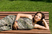 Beautiful pregnant girl lying on bench — Stock Photo