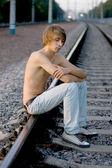 Handsome man walking near rails — Stock Photo