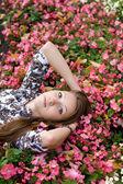 Beautiful girl lying among flowers — Stock Photo