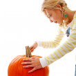 Girl is cutting in big pumpkin — Stock Photo
