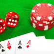 Four aces playing cards and red dice on green background — Stock Photo