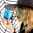 Royalty-Free Stock Photo: Green Halloween witch girl in closeup holding big blue marble