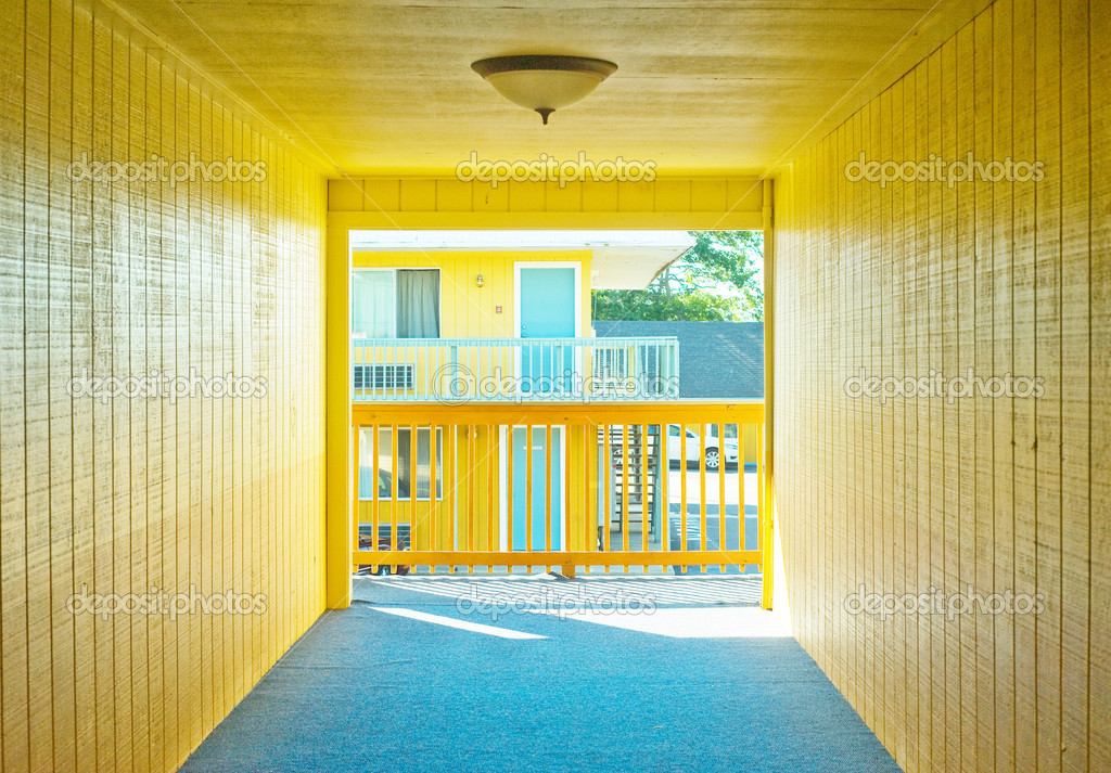 Hallway in a cheap, budget, travel motel lodge with bright yellow walls and blue carpeting. — Stock Photo #7295141