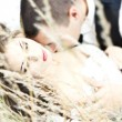 Wedding couple. Bride and  Groom lying in grass and kissing — Stock Photo #7142892