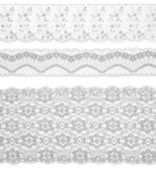 Lace trims ribbon over white. Set of embroidered fabric. Closeup — Stock Photo