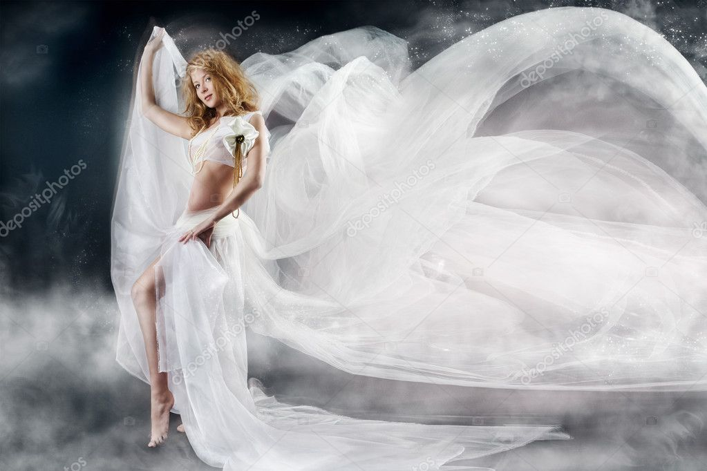 Beautiful woman walking with flying white chiffon fabric, waving  as wings on a wind flow. Mysterious fantasy background — Stock Photo #7142910