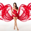 Woman in red flying waving dress as wings on a wind flow. Over w — Stock Photo